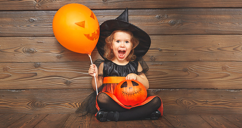 A girl dressed as a witch, holding a balloon and a pumpkin.