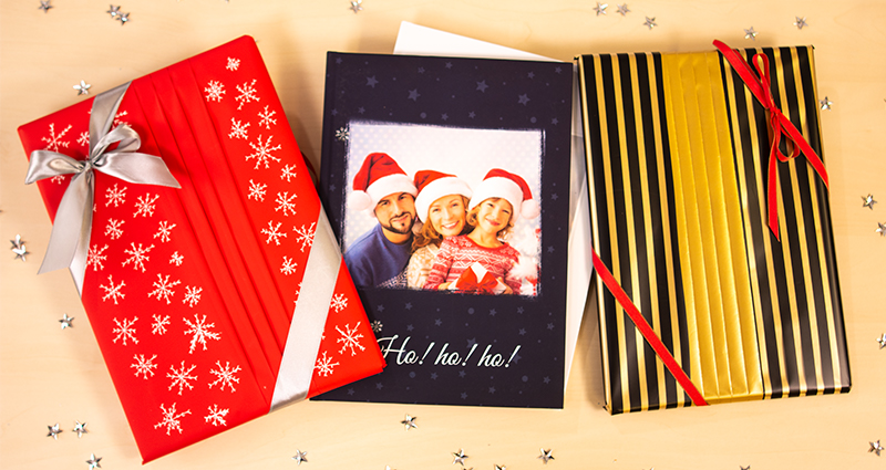 2 photobooks wrapped in a fan-style gift box, a photobook with a navy blue cover and a photo of a smiling family wearing Santa Claus hats in the middle. Silver stars all around them.