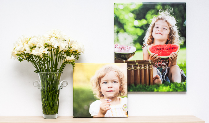 2 spring photo canvases of a small girl next to a flower bucket