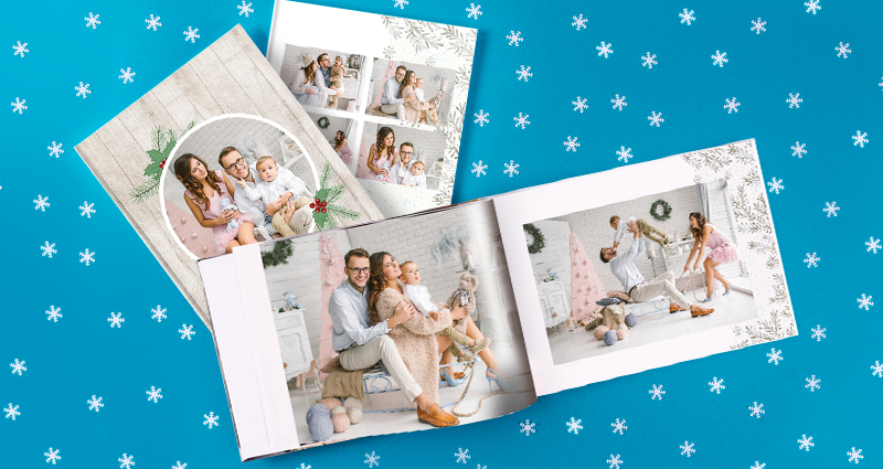 3 Christmas photobooks with family photos – two closed and one open book lying next to tiny stars on the blue background