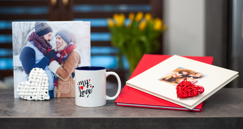 3 photo book types (2 exclusive photo books and 1 classic photo book) on a dark table, a photo mug and a decorative white heart next to them; yellow tulips in a bucket in the background.