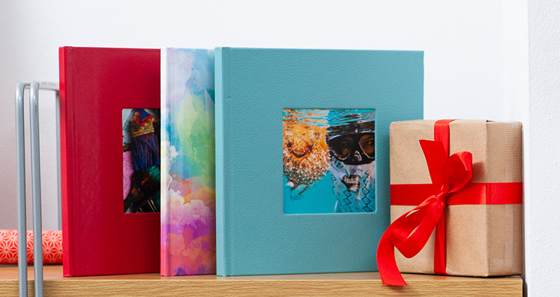 3 square photo books on a wooden shelf (2 exclusive photo books and 1 classic photo book); a gift wrapped with a red bow next to them.