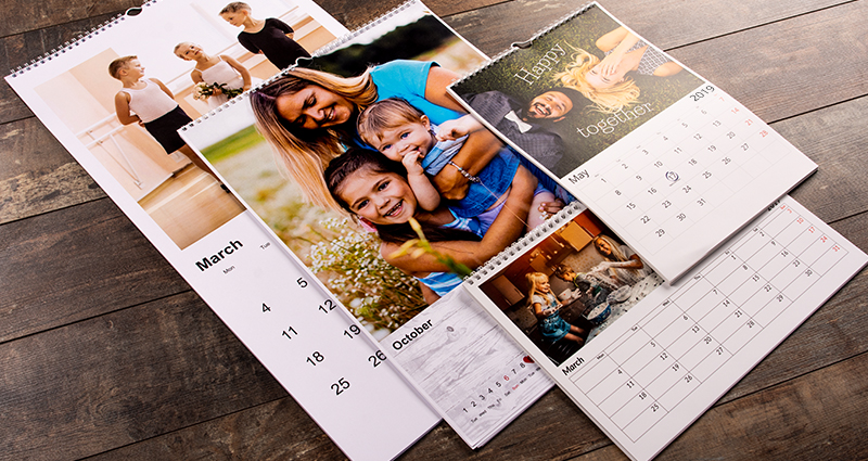 4 Colorland's photo calendars in various formats lying on a floor