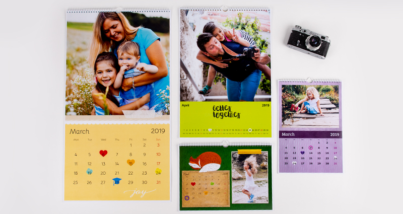 4 photo calendars in various formats on the white background; a camera next to them.