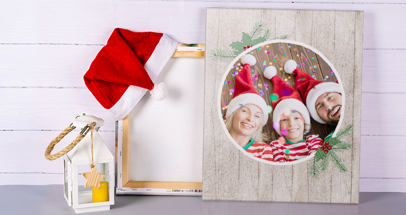 A Christmas canvas next to a white lantern; a wooden wall in the background.