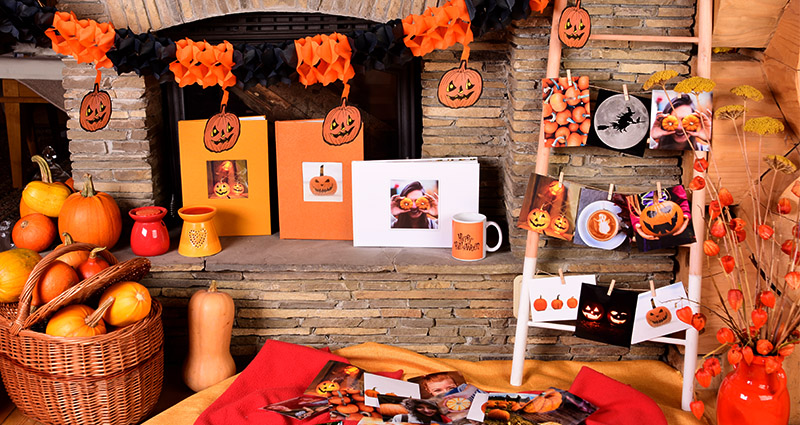 A Halloween arrangement of Colorland products on a fireplace – exclusive photo books, mugs and Insta photos