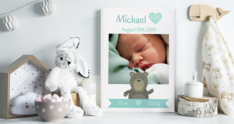 A Photo Canvas with the birth details of a child, placed on a shelf next to teddy bears and decorations