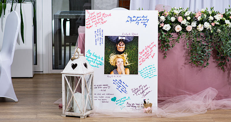 A Photo Canvas with the photo of the newly-weds in the middle with the guests' wishes written with marker pens all around it. A white lantern is standing next to it, a table decorated with powder pink netting and flowers in the background