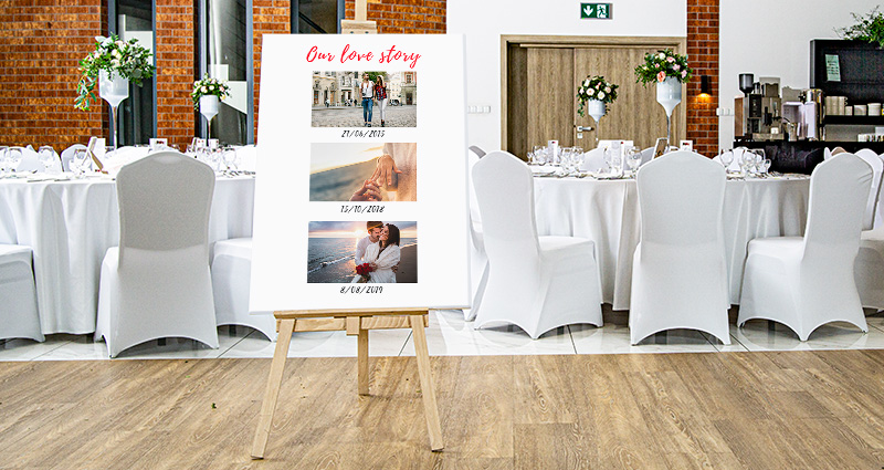 "A Photo Canvas with three photos from different stages of the newly-weds relationship, with a caption ""Our Love Story""  at the top and dates under every picture. Tables ornamented with white decorations in the background"