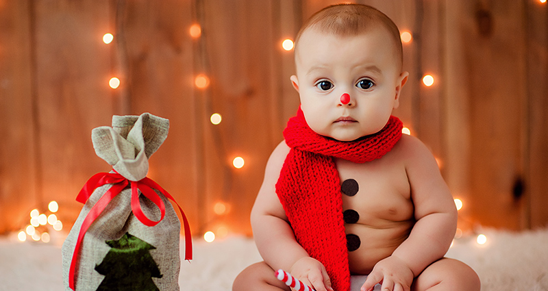 A baby in a red scarf sitting next to a present