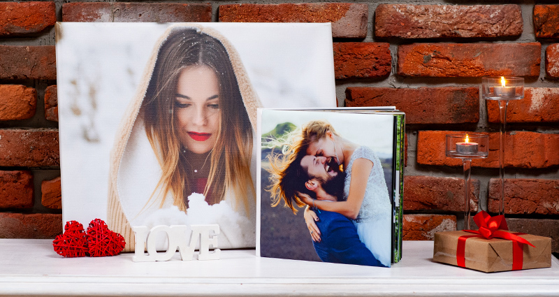 A big photo canvas and a photo album on a white cupboard; a gift wrapped with a red bow, decorative hearts and a wooden LOVE word next to them; a brick wall in the background.