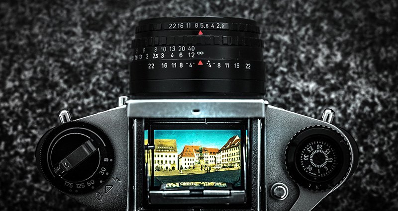 A black camera on the granite background, a photo of a building and blue sky on its screen – a photo taken from above