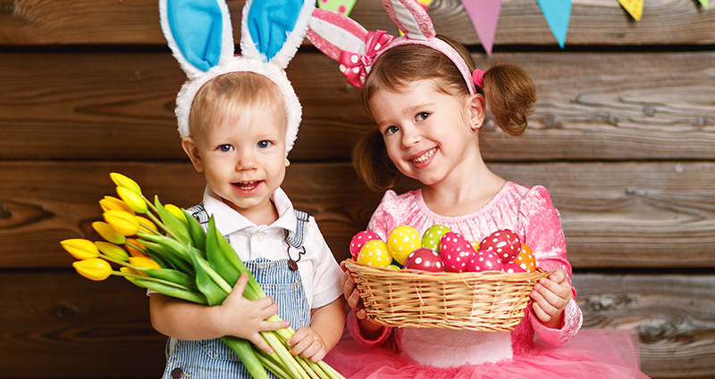 A boy and a girl in bands styled like rabbit ears. The boy is holding a bouquet of tulips and the girl a basket of Easter Eggs. Wooden wall and a colourful festoon as the backdrop.