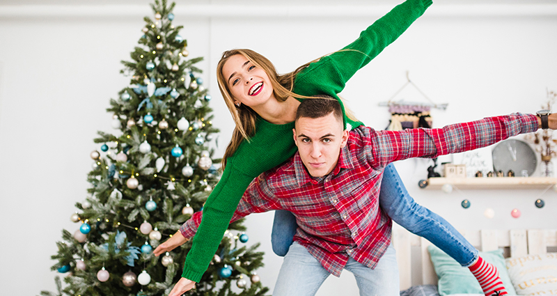 A boy having a girl up on his shoulders. A Christmas tree and a bed in the background.