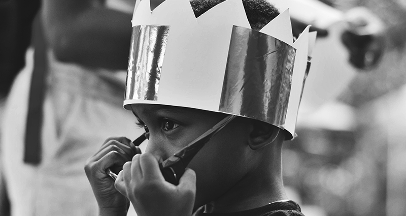 A boy wearing a crown.