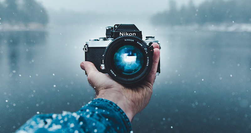A camera held in a hand, on winter background.
