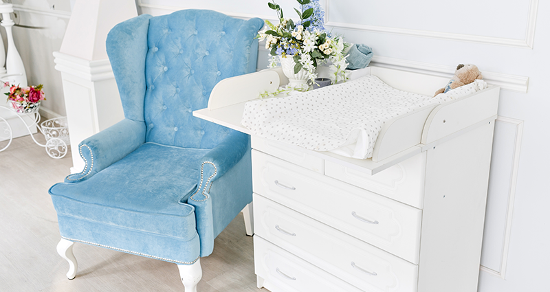 A changing table with a protective mat on the chest of drawers, a blue armchair next to it