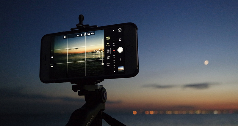 A close up of a smartphone on a tripod. Beach and the sea on the display of the smartphone.