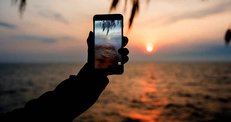 A close up on a man's hand holding a smartphone and taking a photo of a sunset by the sea.