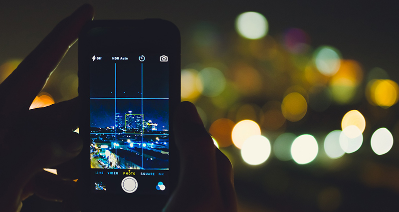 A close up on a smartphone which displays a grid dividing the take into parts, city at night in the background.