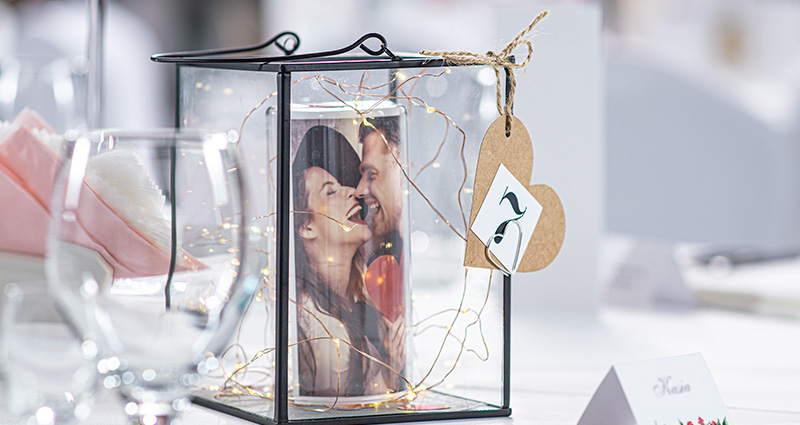 A close-up on a glass lantern standing on a wedding table with a rolled photo, of a couple in love, and led lights inside. Number 7 attached to it.