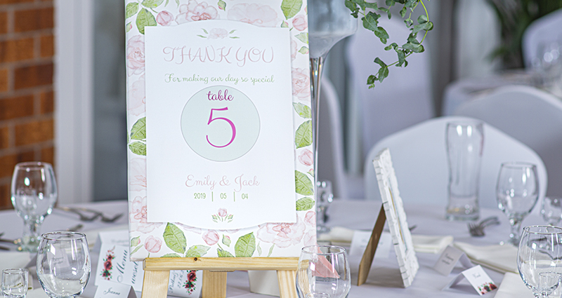 A close-up on a pastel photo canvas with a table number and a thank you note for wedding guests standing on a decorated in white wedding table.