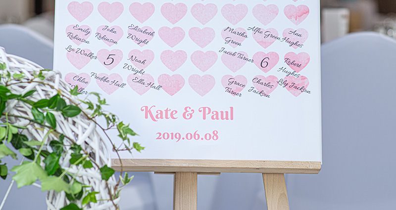 A close-up on a picture of a list of wedding guests on a photo canvas with watercolour heart template on an easel. White tables in the background and a flower decoration nearby.