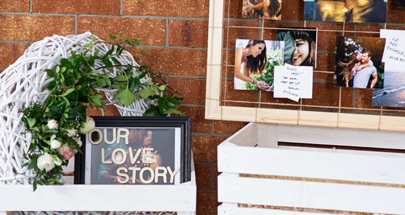A close-up on an 'Our Love' caption in a black frame decorated with flowers in a white box, a part of DIY wooden frame with the photos of the newly-weds from different stages of their relationship placed next to it, with captions next to the pictures. A red brick wall in the background