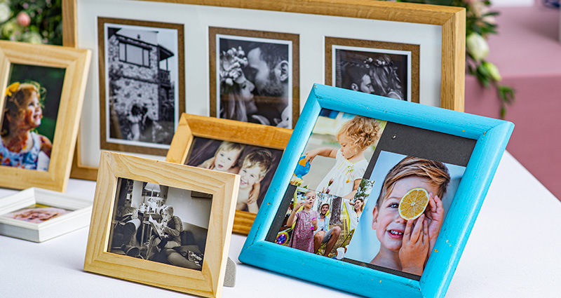 A close-up on colourful frames with photos of the groom, the bride and their families from different stages of life, placed on a table decorated with flowers