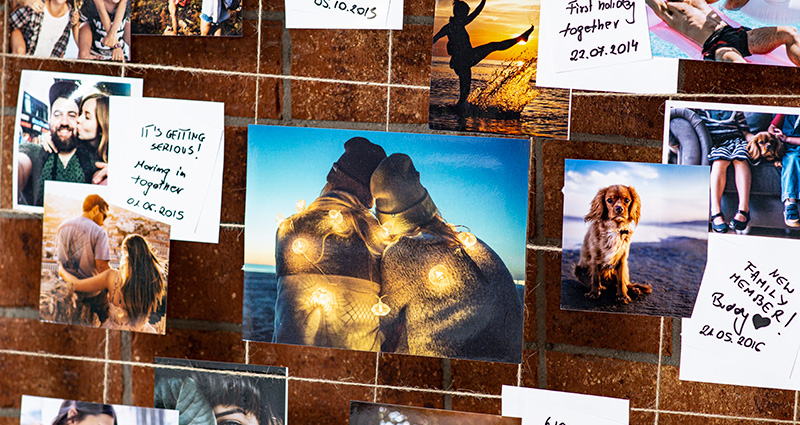 A close-up on the photos of the newly-weds presenting different stages of their relationship, with captions. The photos are attached to a hemp string. A red brick wall in the background