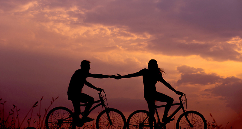 A couple riding on bikes and holding their hands; sunset in pink and orange shades in the background.