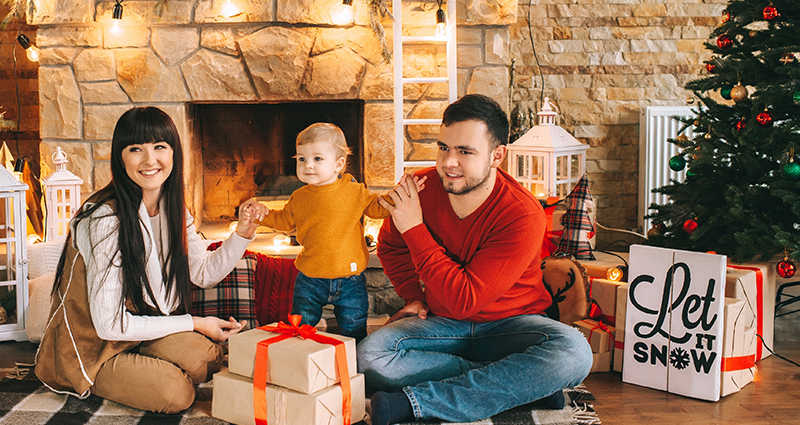 A couple with a small kid sitting on a blanket in front of the fireplace decorated with lights. A Christmas tree and gifts next to them.