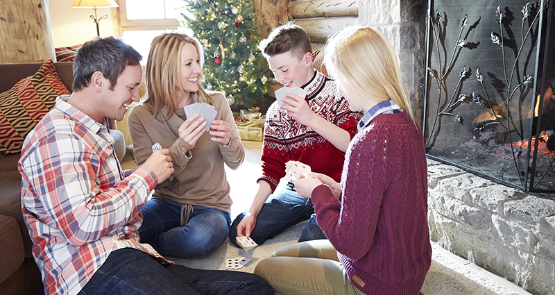 A family playing cards in front of a fireplace on Christmas afternoon