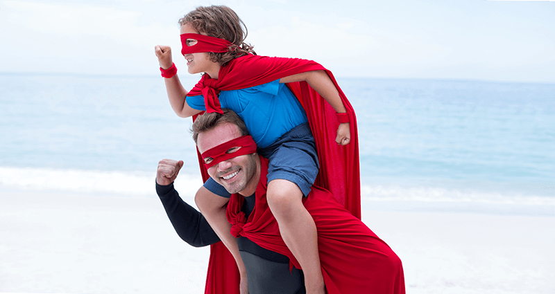 A father with his son, dressed in superman disguises.