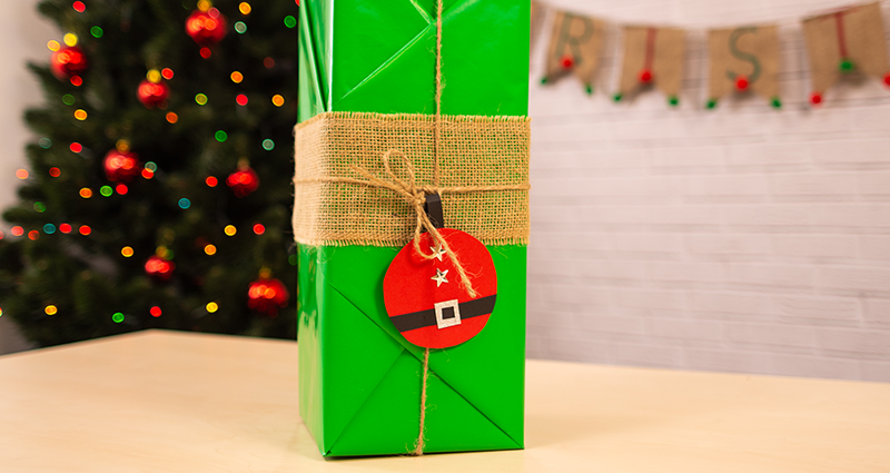 "A gift wrapped in green paper in the Kimono style, tied with some jute and a label in the form of Santa Claus. A Christmas Tree and ""Merry Christmas"" letters in the background."