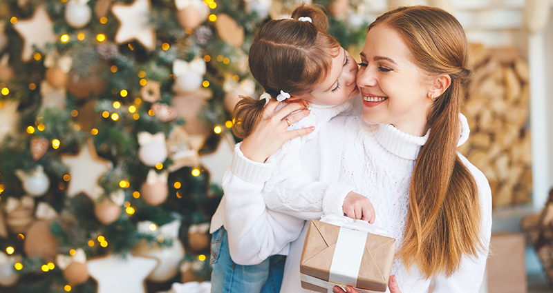 A girl kissing her mum, who is holding a gift, on the cheek, a Christmas tree in the background