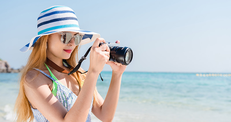 A girl wearing a hat with a photo camera on the beach