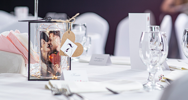 A glass lantern with rolled photo of a couple in love inside and led lights. Number 7 attached to the lantern. The lantern set on a decorated white wedding table. Tableware around.