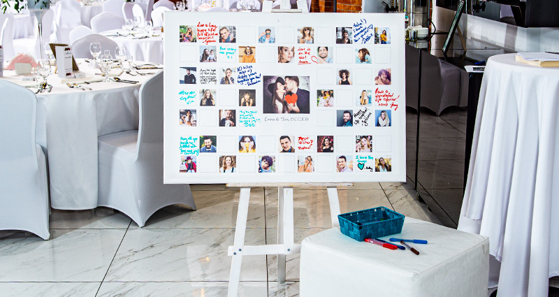 A horizontal canvas with the photo of the newly-weds from their engagement photo shoot in the centre, with the guests' photos all around it and some place for their captions. The Canvas is placed on a white easel, there's a little table in front of it with a little basket for marker pens. Round tables in the background