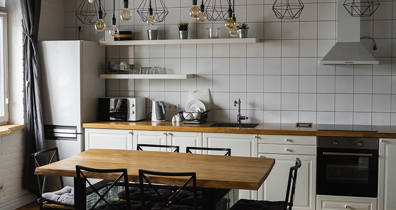A kitchen with square tiles, and geometric lamps