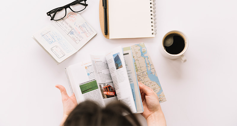 A lay-flat photo: a woman dipping into a travel guide, the passport, a notepad and a mug with coffee are on the desk