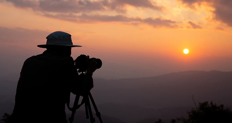 A man wearing a hat, taking a photo at sunset