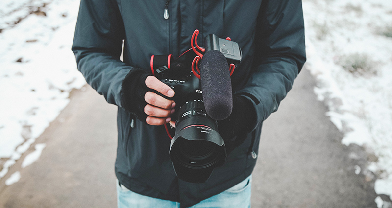 A man wearing fingerless gloves, holding a camera.