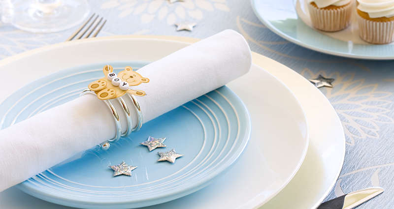 A napkin with a bear pin, placed on a blue plate