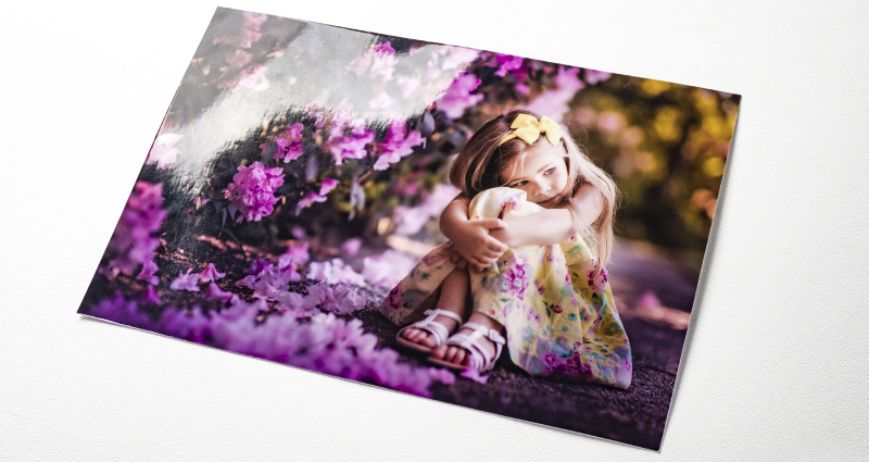 A photo of a girl sitting next to purple flower bushes – a photo printed on the PREMIUM GLOSSY paper.