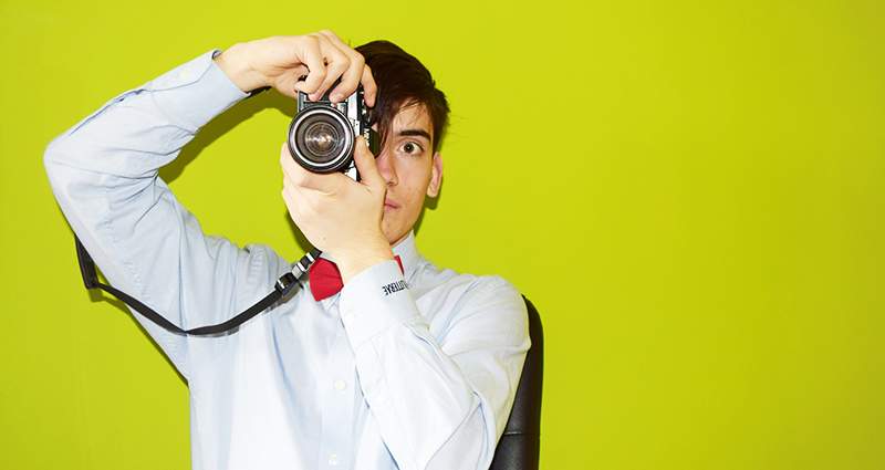A photo of a man wearing a blue shirt with a red bow tie and taking a photo with an analogue camera, a lime wall in the background.
