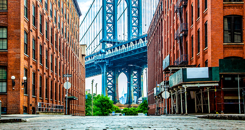 A photo of the Manhattan Bridge taken in a narrow alley between two red-brick buildings.
