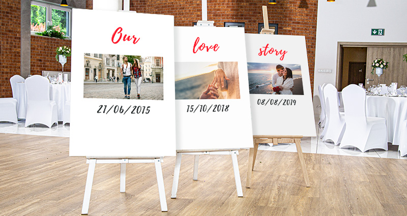 A photo of three photo canvases on easels, presenting photos of the newly-weds from different stages of their relationship, with dates. Round tables in the background