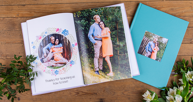 A picture of 2 photo books on a dark wooden background, flowers and decorative plants on both sides. One of the books is open, on its pages pictures of an engaged couple and a caption: 'Thanks for teaching us how to love!'. Closed photo book with a turquoise eco leather cover and a photo of the same couple in a photo slot.