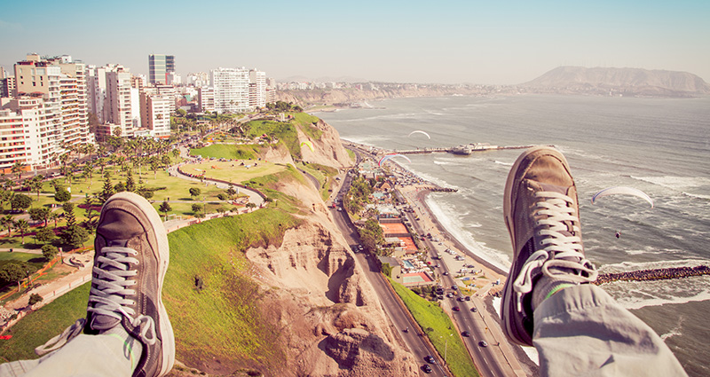 A picture of a modern city by the coast, legs of a man sitting on the edge in the foreground